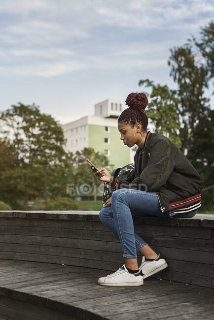 Side view of beautiful teenage girl using smartphone in park — Stock Photo