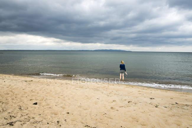 Vista posteriore della donna sulla spiaggia sabbiosa guardando il mare — Foto stock