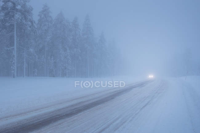 Faróis na estrada coberta de neve — Fotografia de Stock