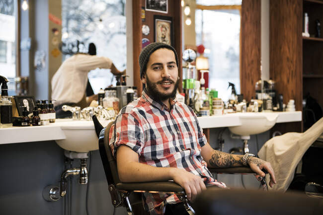 Retrato de peluquero sentado en silla y mirando a la cámara - foto de stock