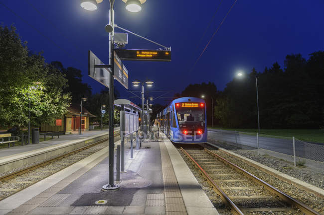Train arriving at station at night in Lidingo, Sweden — Stock Photo