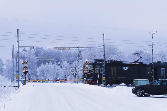 Auto wartet auf schneeglatter Straße an Bahnübergang — Stockfoto