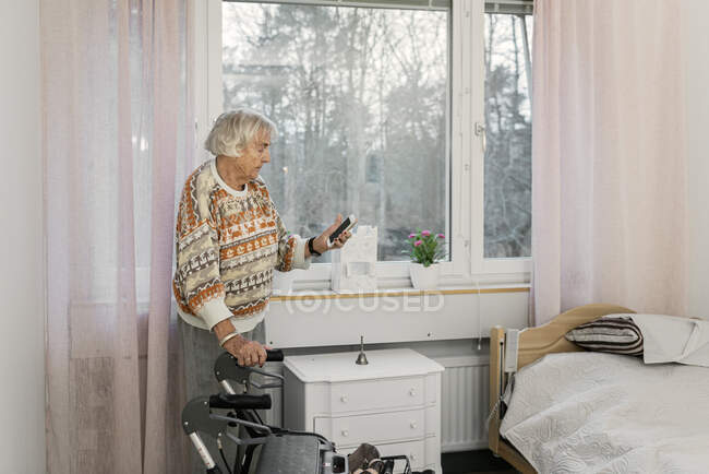Senior woman using smartphone by window — Stock Photo