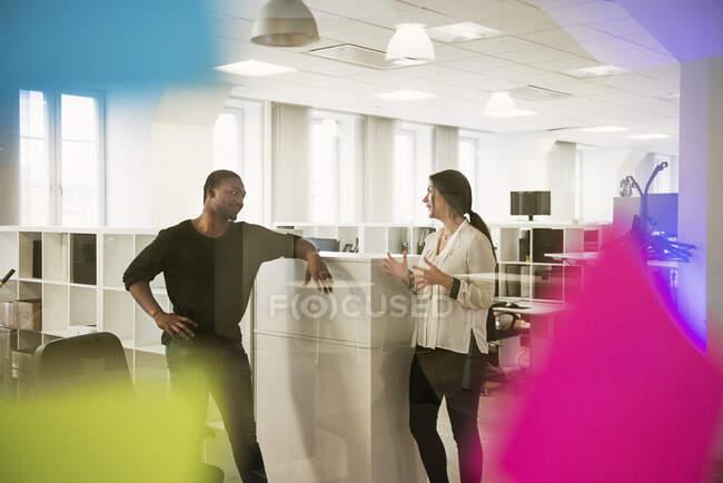 Junge multiethnische männliche und weibliche Mitarbeiter sprechen im Büro — Stockfoto
