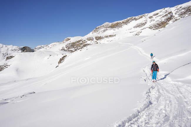 Männer beim Skifahren in schneebedeckten Bergen — Stockfoto
