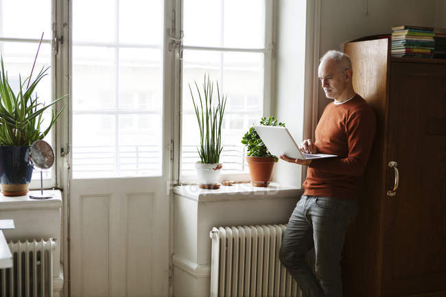 Senior benutzte Laptop am Fenster — Stockfoto