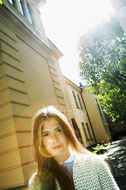 Портрет девочки-подростка против здания, линзы вспышки — стоковое фото