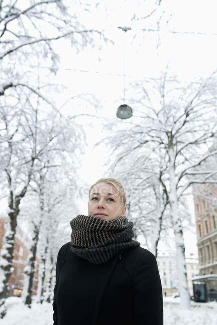 Young woman on snowy city street, focus on foreground — Stock Photo