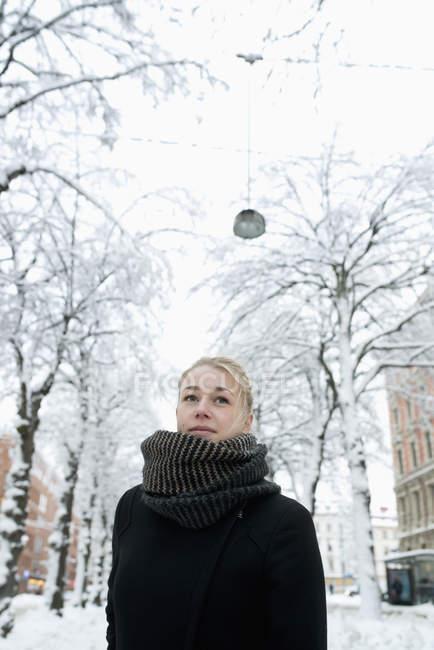 Junge Frau auf verschneiter Stadtstraße, Fokus auf den Vordergrund — Stockfoto