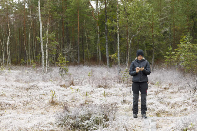Mature woman standing in front of forest — Stock Photo