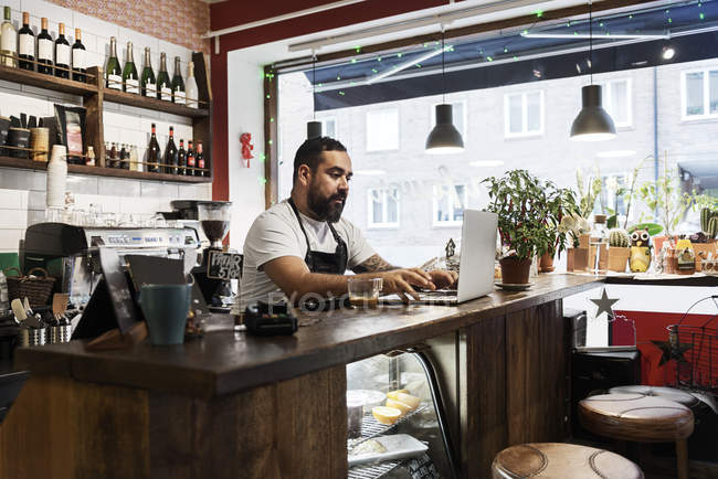 Mid adult man working in cafe — Stock Photo