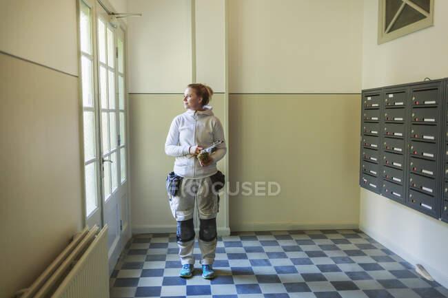 Peintre debout près des boîtes aux lettres et regardant de côté dans un immeuble d'appartements — Photo de stock