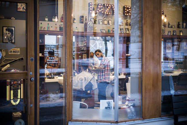 Vista a través de la ventana de peluquería corte de pelo del cliente - foto de stock