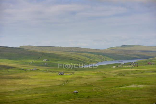 Verde llanura y lejano parche de mar en las Islas Shetland, Reino Unido - foto de stock