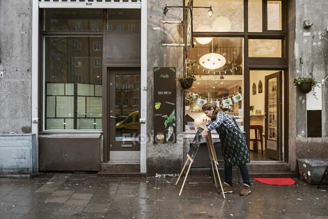 Кафе власник пише знак, вибірковий акцент — стокове фото