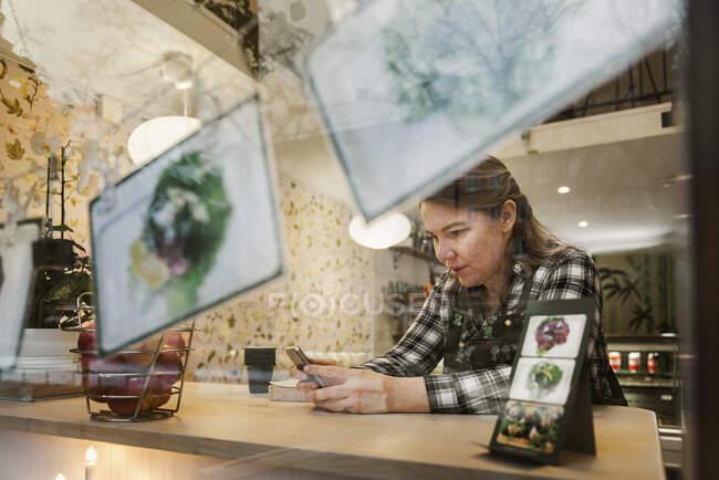 Mujer que utiliza smartphone en la cafetería, vista a través del cristal. - foto de stock