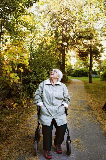 Пожилая женщина сидит на пешеходной раме в парке — стоковое фото