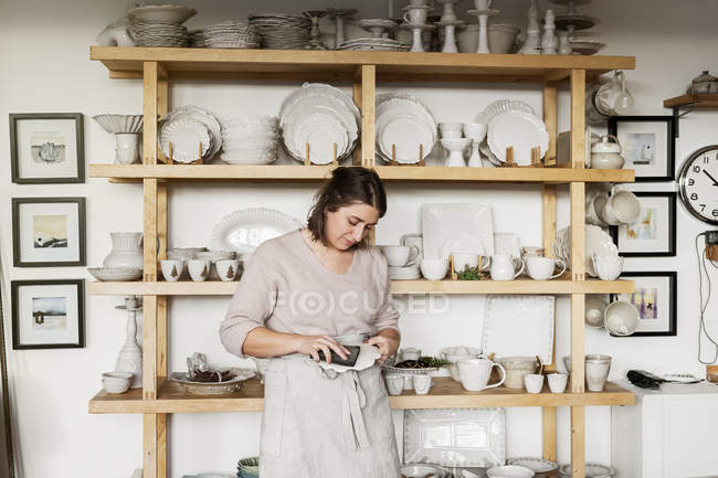 Woman cleaning pottery, selective focus — Stock Photo