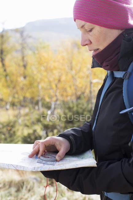 Женщина, использующая компас и карту, избирательный фокус — стоковое фото