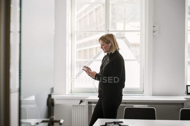Woman listening music on earphones from smartphone in office — Stock Photo