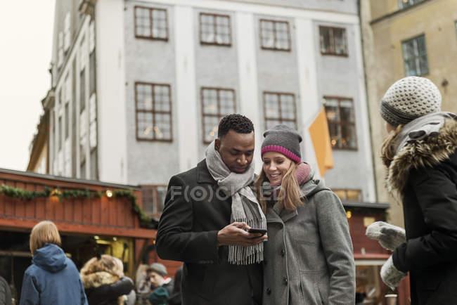 Coppia guardando smartphone nel mercato, messa a fuoco selettiva — Foto stock