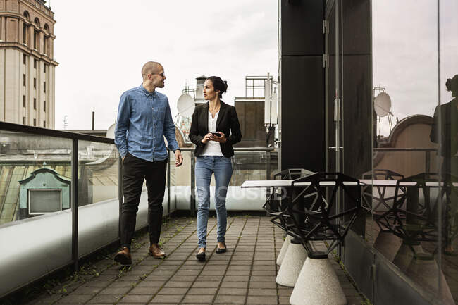 Friends talking while walking on balcony, full length view — Stock Photo