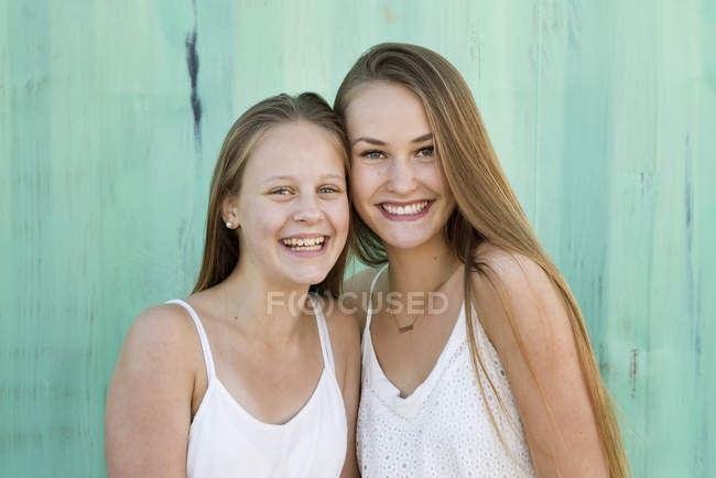 Portrait of sisters smiling, focus on foreground — Stock Photo
