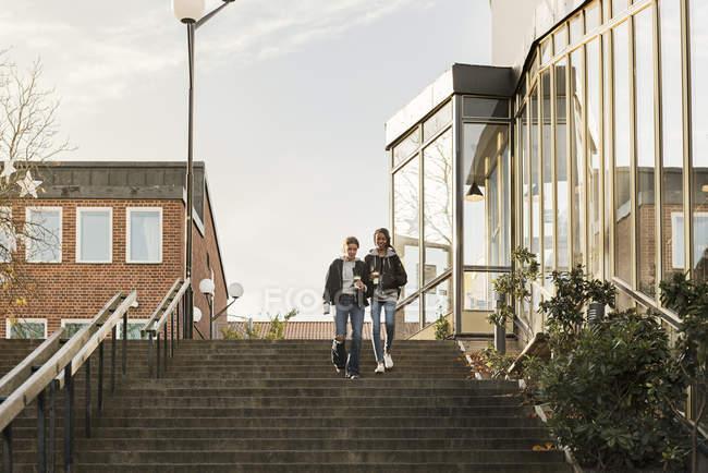 Adolescentes avec des tasses à café dans un escalier — Photo de stock