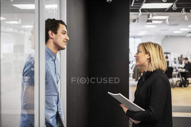 Coworkers talking in office, focus on foreground - foto de stock
