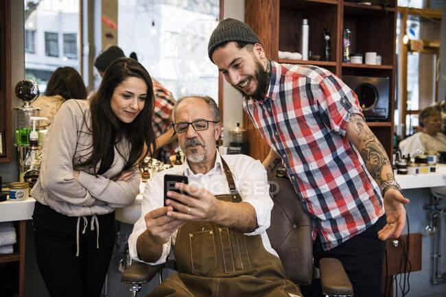 Barberos sonrientes masculinos y femeninos mirando el teléfono inteligente - foto de stock