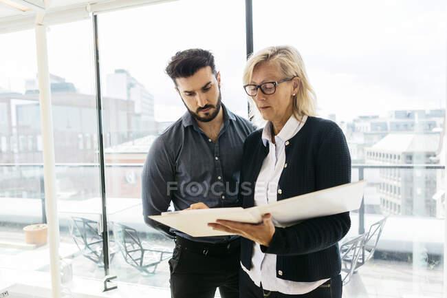 Des gens d'affaires avec un dépliant discutant de leur travail au bureau — Photo de stock