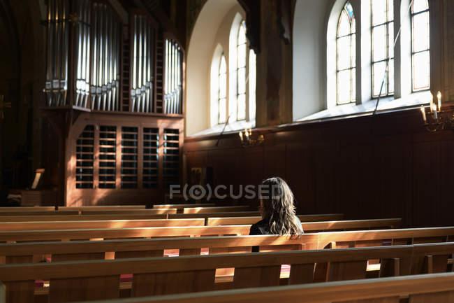 Sacerdote sentado en el banco en la iglesia, enfoque selectivo - foto de stock