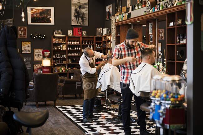 Barbiers couper les cheveux des clients dans le salon de coiffure — Photo de stock