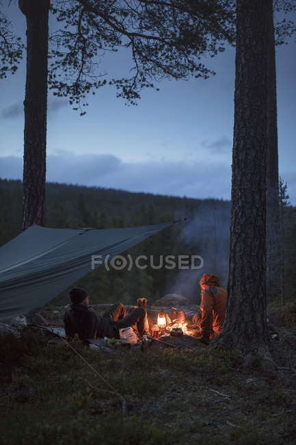 Men by campfire, selective focus — Stock Photo