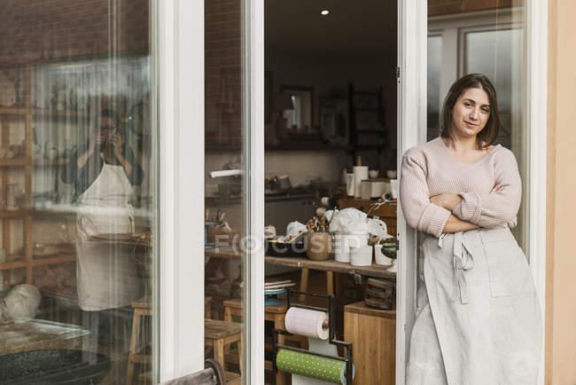 Женщина, прислонившаяся к двери керамической мастерской — стоковое фото