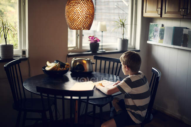Boy reading book while sitting at dining table — Stock Photo