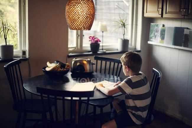 Cahier de lecture d'un garçon assis à la table — Photo de stock