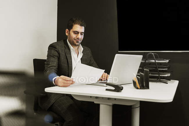 Young man sitting at desk and working with laptop in office — Stock Photo