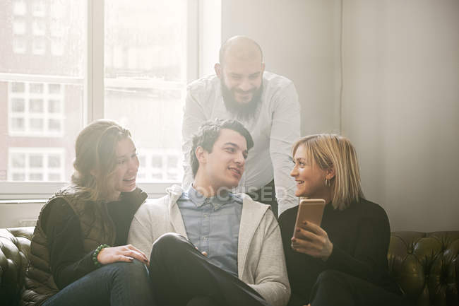 Coworkers looking at smart phone and talking — Stock Photo