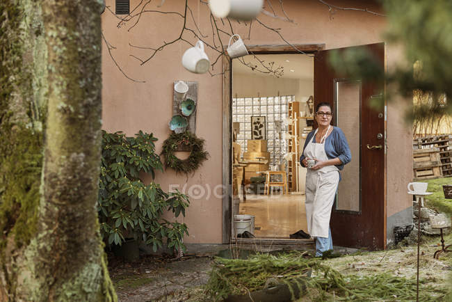 Woman wearing apron by mugs hanging from tree — Stock Photo