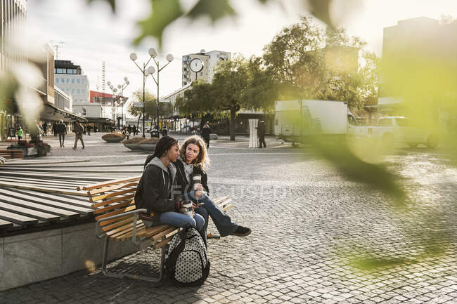 Teenage girls sitting on bench on street, selective focus — Stock Photo