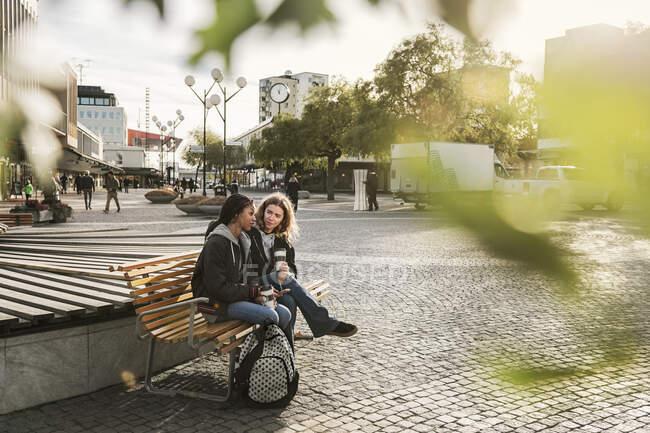 Adolescentes assises sur un banc dans la rue, approche sélective — Photo de stock
