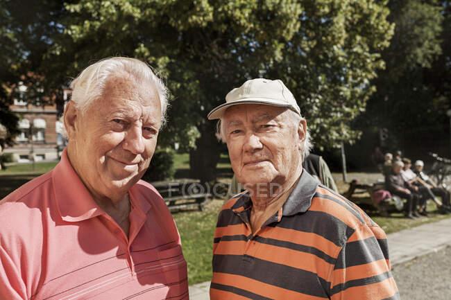 Портрет пожилых людей, стоящих вместе и смотрящих в камеру на улице — стоковое фото