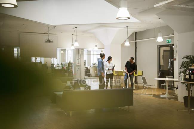 Коллеги разговаривают в офисе, избирательный фокус — стоковое фото