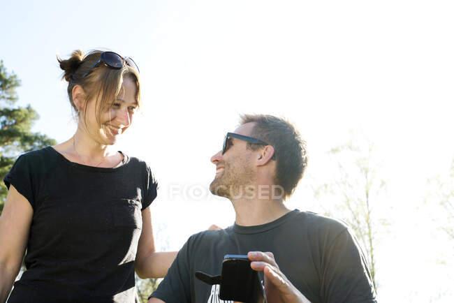 Casal sorrindo uns aos outros e usando smartphone ao ar livre — Fotografia de Stock