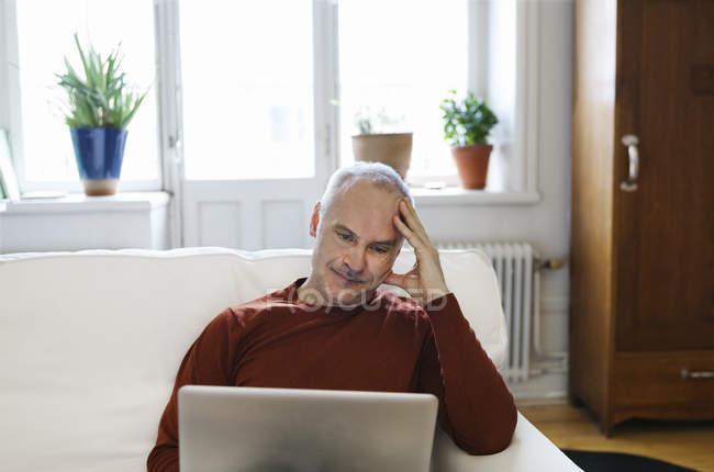 Uomo anziano che utilizza il computer portatile, concentrarsi sul primo piano — Foto stock