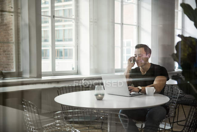 Young man using laptop and talking on phone, selective focus — Stock Photo
