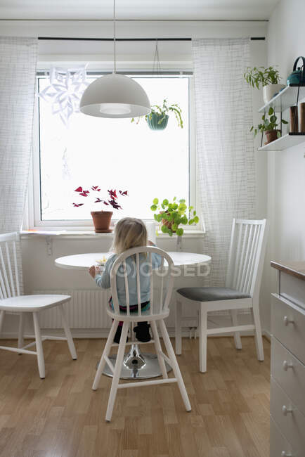 Back view of cute little girl sitting at a table — Stock Photo