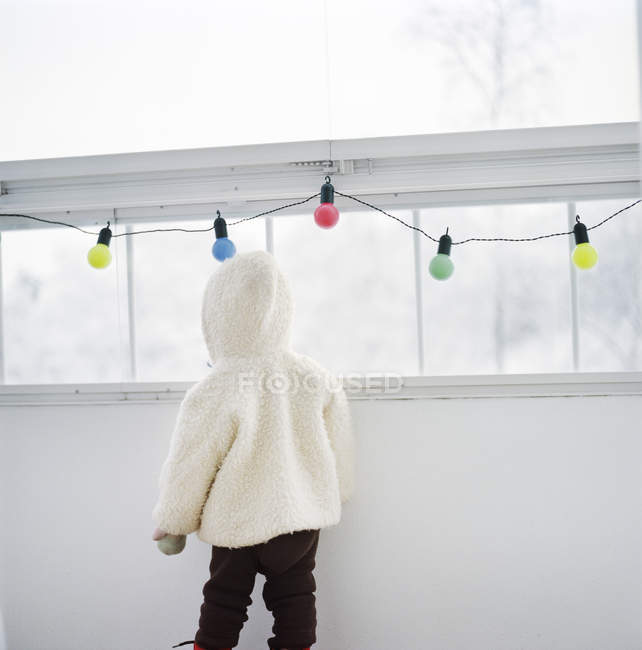 Rear view of child in warm clothes indoors — Stock Photo
