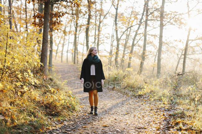 Mulher que anda na floresta outonal — Fotografia de Stock